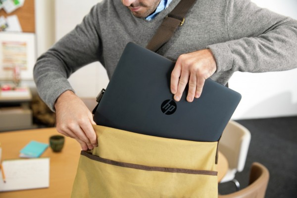 Man inserting the HP EliteBook 840/845 into messenger bag